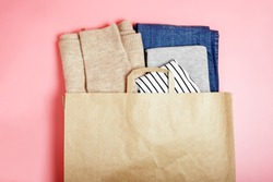 Craft brown paper bag with clothes (blue jeans, beige sweater, gray t-shirt, white shirt) on a pink background. Shopping concept, seasonal sale. Background for text, copy space.
