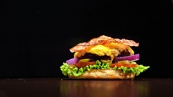 Craft burger is cooking on black background in black food gloves. Consist: sauce, lettuce, tomato, red onion, pickle, cheese, bacon, air bun and marbled meat beef. Not made ideal. Looks real, loving