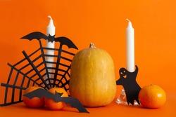 craft Halloween.candles, pumpkin, spider web, bat on an orange background halloween holiday, invitation