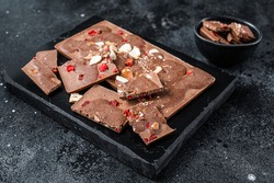 Craft homemade chocolate bars chopped on marble board. Black background. Top view.