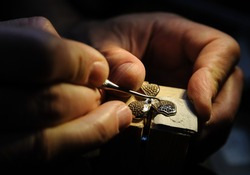 Craft jewelery making. Jeweler fixes sapphires on the ring.