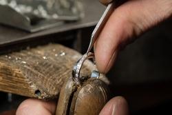 Craft jewelery making.  Repairing ring by inlaid tight gem.