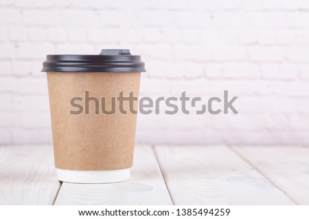 1af28570a1b Craft paper coffee cups on a white table near light wall background  #1385494259