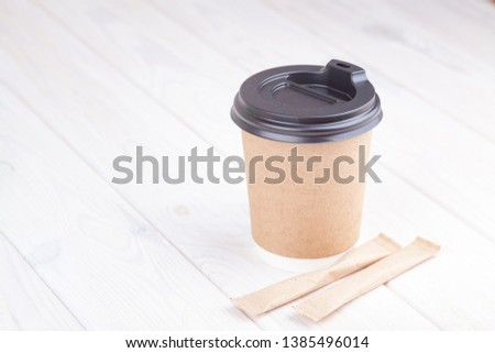 b07ef58001e Craft paper coffee cups on a white table near light wall background  #1385496014