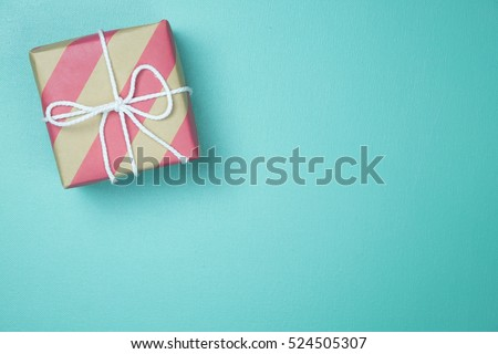 Craft paper wrapped present box craft rope bow ribbon on blue background, top view #524505307