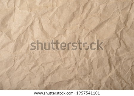Craft wrapping paper. The texture of a flat crumpled sheet of cellulose products. Old tattered page surface background. Eco-friendly empty aged recyclable packaging. Photo stock ©