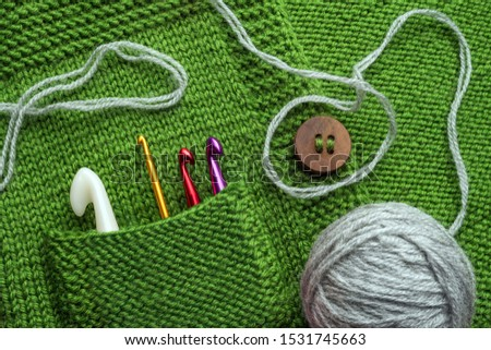 Crafted concept. Handmade background. Crochet hooks in green pocket. Fragment of handmade clothing with hooks in the pocket. Wooden buttons on handmade sweater. Stylish clothing crafted, handmade