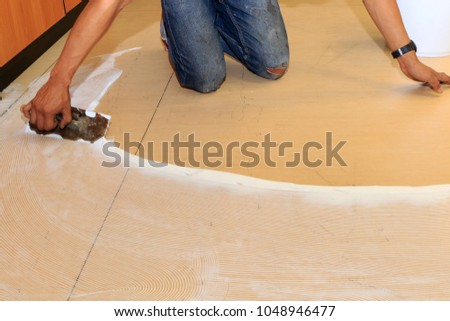 Craftman hands glue the floor for laying a new material floor. Repair and renovation interior office building. #1048946477