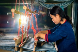 Crafts and craftsmanship. Traditional Isan Thai Cotton indigo weaving.  Young woman weaving Cotton Indigo in traditional way at manual loom. Thailand . Selective focus.