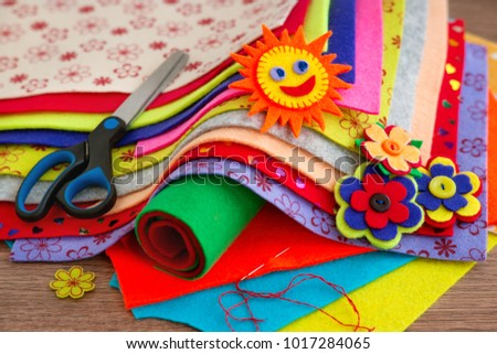 Crafts and creativity of felt. Multicolored felt sheets for making crafts. Scissors, bright felt, needle and thread for needlework. The sun and flowers are crafts made of felt.