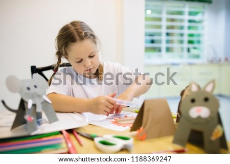 Crafts for kids. Child making colorful paper animals at art class. Creative little girl with glue stick and scissors creating do it yourself toys. Children crafting. School kid doing craft homework.