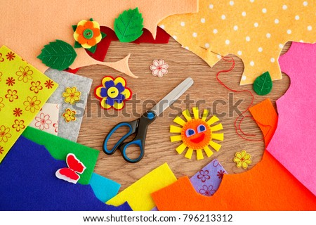 Crafts from colorful felt. Flowers, butterflies, sun, leaves are made of felt. View from above. Scissors and a needle with a thread are needed for sewing crafts made of felt. Felt and needlework.