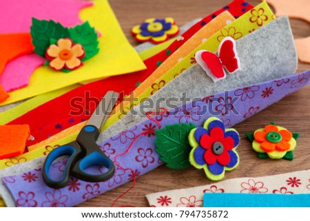 Crafts made of felt. Multicolored bright felt and hand-made articles. Flowers and butterfly made of felt. Felt for needlework and handwork. Scissors and needle for sewing.