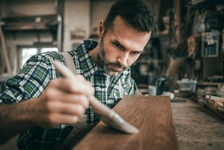 Craftsman applies varnish on wooden board by paintbrush in his carpentry workshop