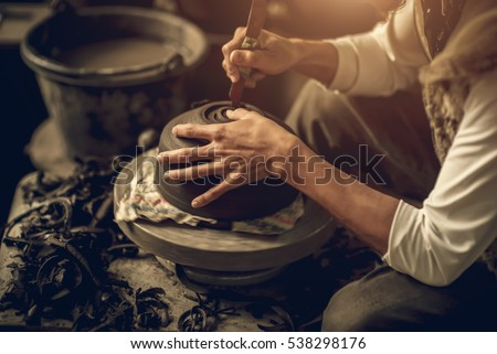 Craftsman artist making craft, pottery, sculptor from fresh wet clay on pottery wheel, selected focus