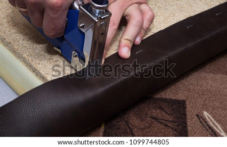 Craftsman fastening brown leather to the paricle board using staples and blue stapler
