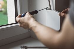 craftsman fixing the window and roller blinds with screwdriver. Builder installing a shutter and window in a house.