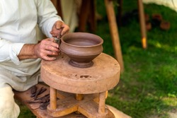 Craftsman hand making pottery from clay on potters wheel at historical reenactment of Slavic or Vikings lifestyle around 11th century, Cedynia, Poland