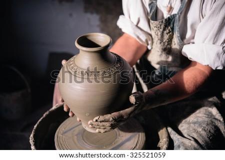 Craftsman holding a clay vase in his workshop; Potter holding ceramic vase.