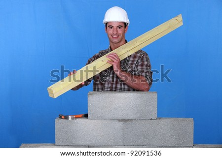 craftsman holding two wooden boards