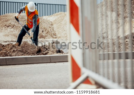Craftsman in reflective vest and white helmet digging in sand