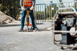 Craftsman in uniform with drill repairing asphalt during roadwork
