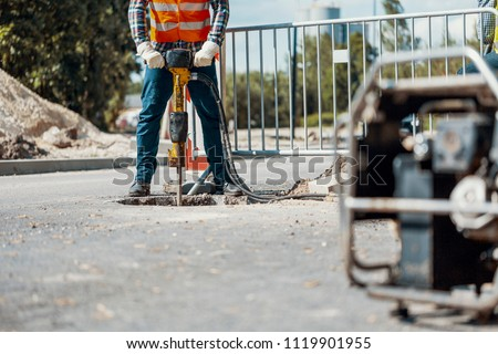Craftsman in uniform with drill repairing asphalt during roadwork