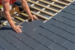 Craftsman is installing a slate roof. Professional roof workers installing roof for a old house .Working on rooftop.