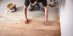Craftsman lays parquet floor and spreads the glue on the screed and beats the floorboards with the hammer and the block