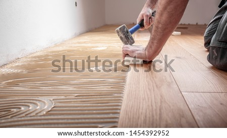 Craftsman lays parquet floor and spreads the glue on the screed and beats the floorboards with the hammer and the block Photo stock ©