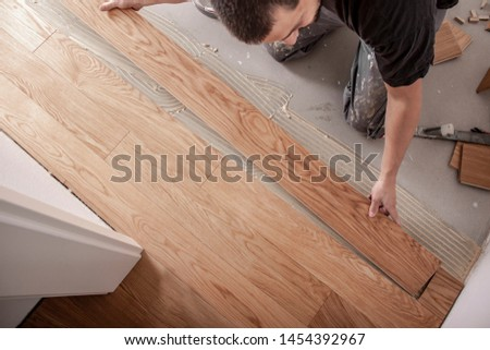 Craftsman lays parquet floor and spreads the glue on the screed and beats the floorboards with the hammer and the block Stock photo ©