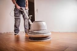 craftsman oils parquet floor with big polishing machine