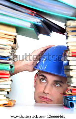 craftsman overwhelmed with paper work - stock photo