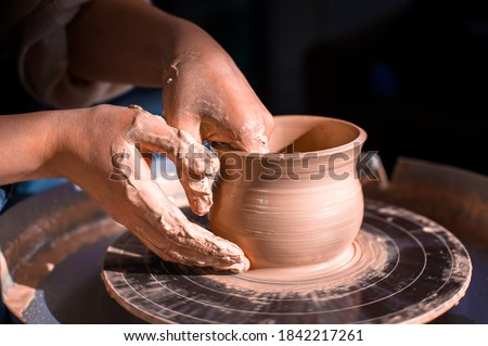 Craftsman's hands and potter's wheel. Close-up. Stock fotó ©