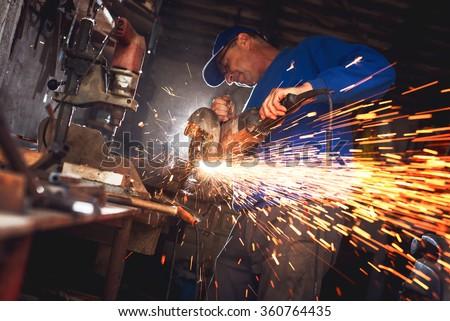 Craftsman sawing metal with disk grinder in workshop.