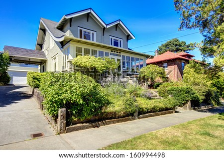 Craftsman style American old house with front porch and large garage on the back.