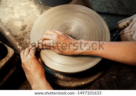 Craftsman use a sponge to wipe the clay on potter's wheel. Cleaning the pottery wheel. Ceramics art concept. Artistic creative. Selective focus. #1497101633