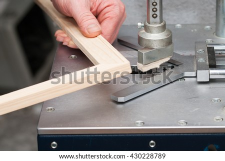 Craftsman working on frame in frame shop. Professional framer hand holding frame angle. Top view.