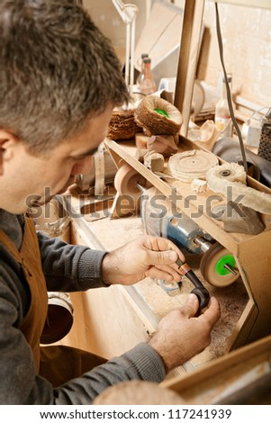 Craftsman working on grinder finishing smoking pipe