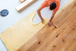 Craftsmen lay parquet flooring in a modern house
