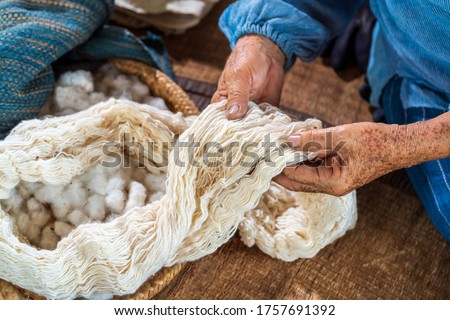 Craftsmen of Thai indigo cotton. An elderly woman is examining the thread made of cotton. Local Master are the original Indigo Cotton Weaving in the community of Sakon Nakhon province.