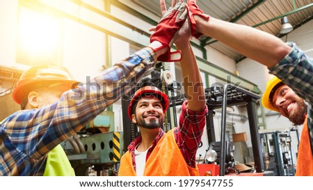 Craftsmen team is successful and makes high five motivation in a factory hall Stock photo ©