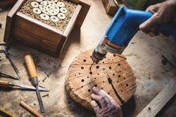 Craftsperson making wooden insect house. Carpenter using drill in workshop. Manual worker doing decorative insect hotel