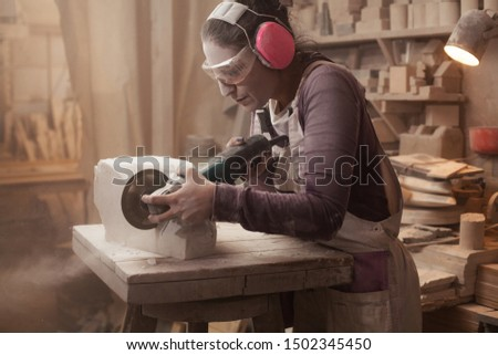 Craftswoman cutting a piece of white marble stone with an angle grinder, female sculptor at work in an artisan workshop