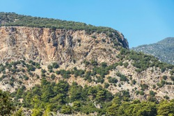 Crag with rock-cut tombs towering over ruins of ancient Lycian city of Pinara.