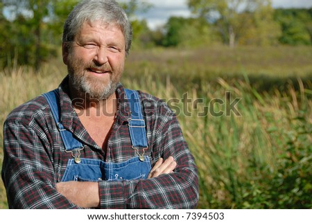 craggy farmer, arms crossed, smiling - stock photo