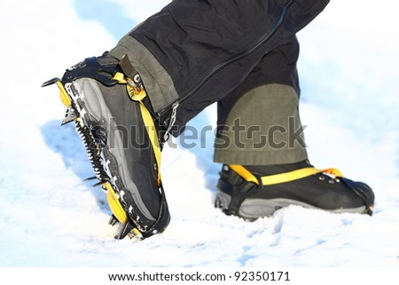 Crampons and shoes walking on ice and snow during outdoor winter trekking. Close up.