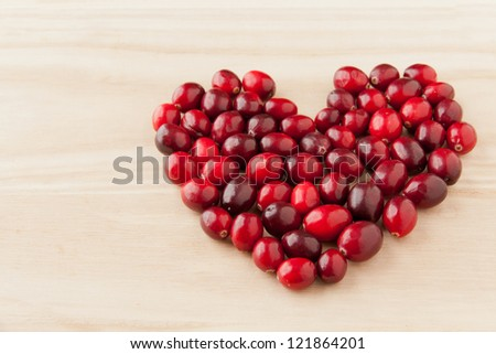 Cranberries in heart shape on wooden board, healthy vitamin food. selective focus - stock photo