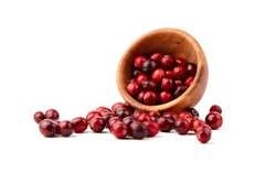 Cranberries in wooden bowl isolated on white background. Fresh red ripe cranberris, autumn berries scattered on white