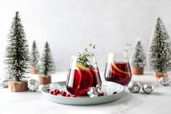 Cranberry gin boozy cocktail with grapefruit and thyme served on winter holidays decorated table, front view